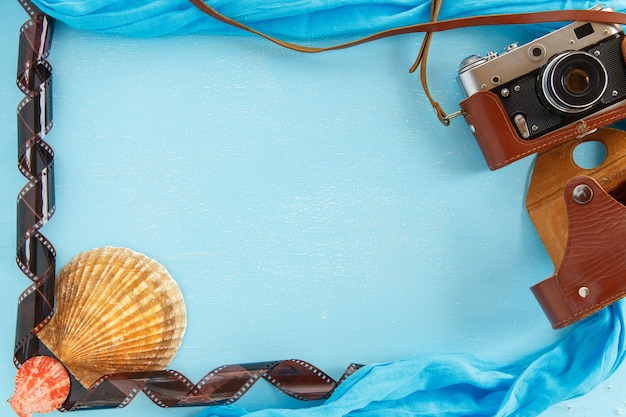 Blank paper photo frame with starfish, shells and items on wooden table.