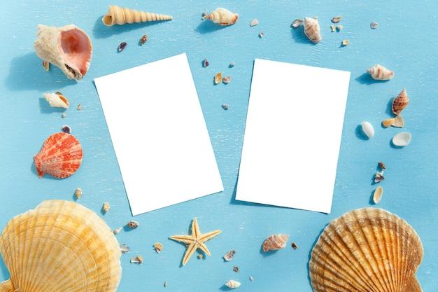ヒトデ、貝殻、木製のテーブル上のアイテムの空白の紙フォトフレーム。
