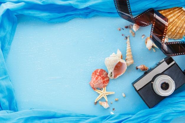 Рамки для фотографий чистого листа бумаги с морскими звёздами, ракушками и предметами на деревянном столе.