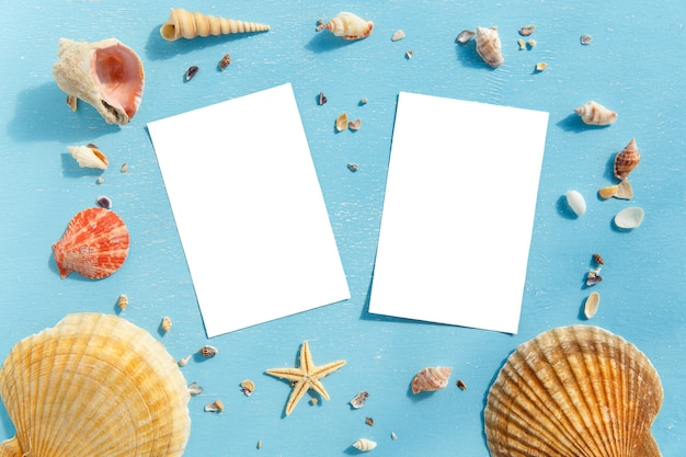 Blank paper photo frames with starfish, shells and items on wooden table.