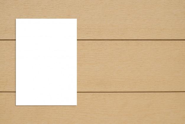 Плакат чистого листа вися на деревянной стене.