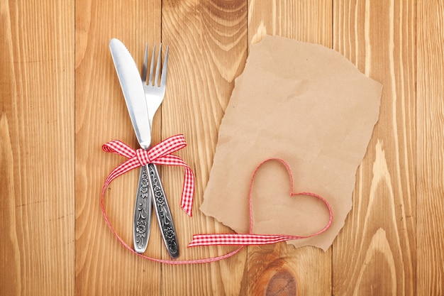 Blank paper for recipe or note and silverware on wooden table background