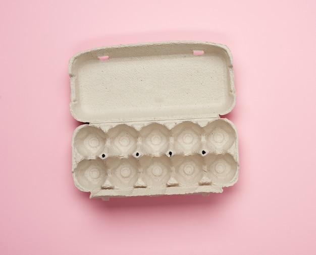 Чистый прямоугольный лоток для куриных яиц на розовом