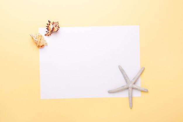 빈 종이, 조개 및 노란색 배경에 불가사리. 여름 방학 및 휴가 계획의 개념