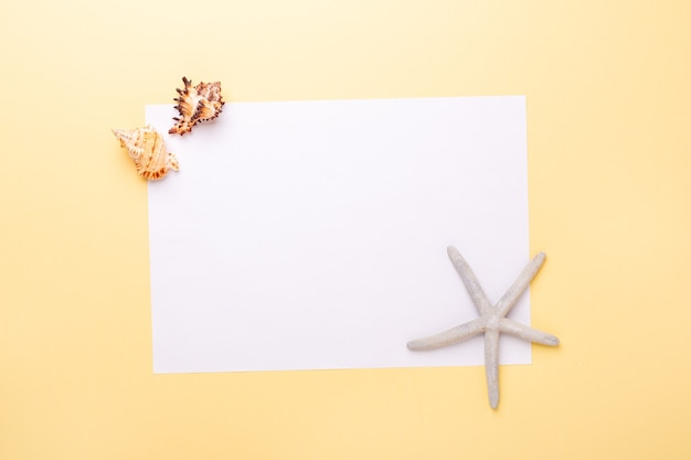Blank paper, seashells and starfish on yellow background. concept of planning summer holidays and vacation