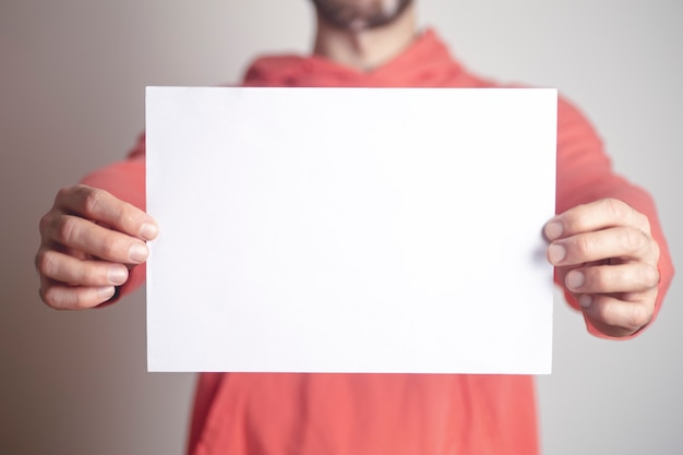 A blank paper sheet background in the hands of a young man.