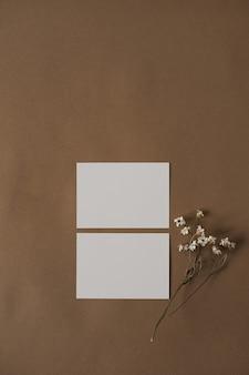 美しい白い花と白紙のシートカード。深いパステルベージュブラウンの美的ミニマルビジネステンプレート