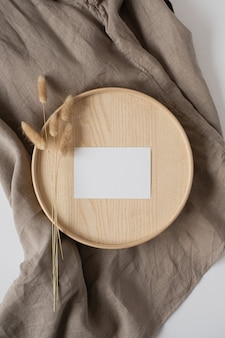 Blank paper sheet card with bunny tail on wooden casket and grey linen blanket.