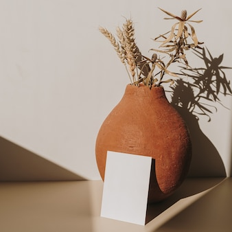 Пустой лист бумаги с глиняным горшком с букетом сухой пшеницы с тенью солнечного света на белом