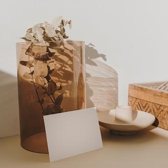 ベージュの日光の影の黄褐色のガラスの花瓶に乾いたユーカリの枝が付いた白紙のシートカード