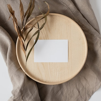 Blank paper sheet card with dry flowers on wooden casket and grey linen blanket.