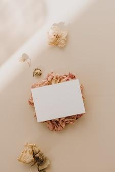 Открытка с чистым листом бумаги с цветочными бутонами с тенями солнечного света на бежевом