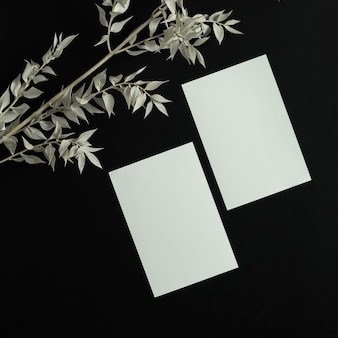 Blank paper sheet card with mockup copy space and dry floral branch on black background.