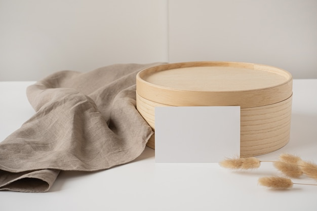 Blank paper sheet card with rabbit tail grass, wooden casket and grey linen blanket