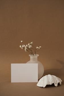 Пустая карточка листа бумаги с ракушкой, красивыми белыми цветками против нейтральной коричневой стены.