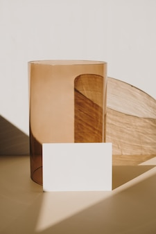 白地に日光の影と黄褐色のガラスの花瓶と白紙のシートカード