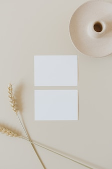 コピースペースとベージュの小麦ライ麦の茎が付いた白紙のシートカード。最小限のビジネスブランドテンプレート。フラットレイ、上面図