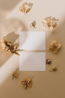 Открытки с чистым листом бумаги с сухими цветочными бутонами с тенью солнечного света на бежевом
