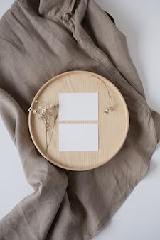 木製の棺と灰色のリネンの毛布にドライフラワーと白紙のシートカード