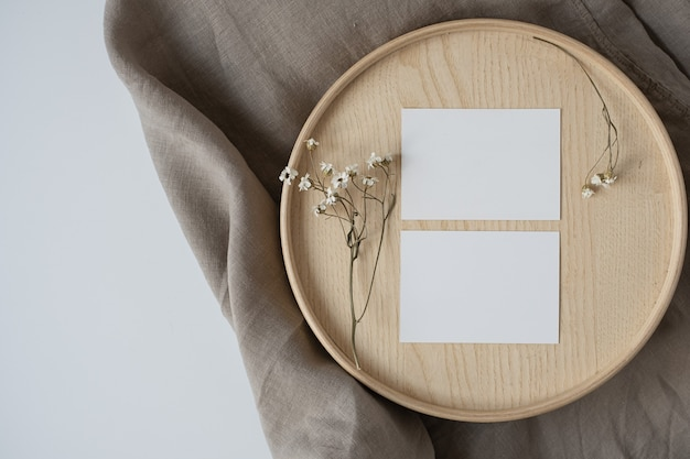 Blank paper sheet cards with dry flowers on wooden casket and grey linen blanket