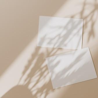 Пустые листы бумаги с копией пространства для макета с тенью солнечного света на бежевом