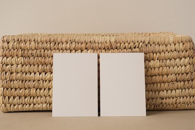 Карточки листа чистого листа с шкатулкой из ротанга против нейтральной белой стены.