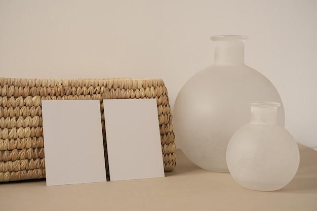Пустые листы бумаги с шкатулкой из ротанга, ваза на нейтральной белой стене