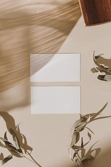 木製トレイとベージュの日光の影と乾燥した葉を持つ空白の紙シートカード