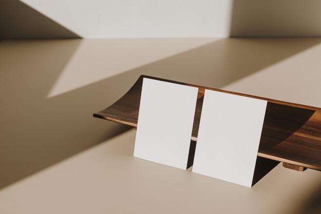 Пустые листы бумаги с деревянным подносом с тенью солнечного света на бежевом столе