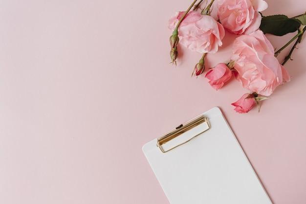 Блокнот сзажимом для бумаги листа бумаги, букет розовых цветов на розовом фоне. flatlay, вид сверху