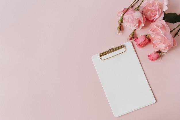 空白の紙シートクリップボードメモ帳、ピンクの背景にバラの花の花束。フラットレイ、上面図