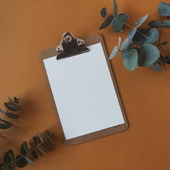 深いオレンジ色のユーカリの枝が付いている空白の紙シートクリップボードパッド