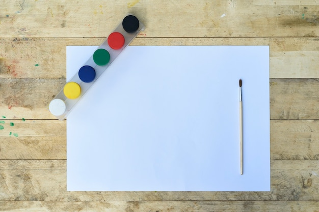 Чистый лист бумаги, гуашь и кисть. подготовка к покраске