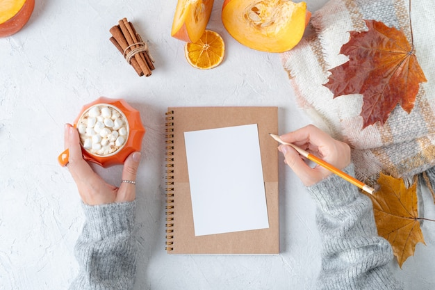 Blank paper sheet over notebook with woman's hands in sweater and pumpkins cup.