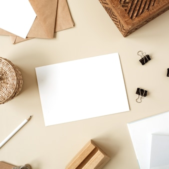 베이지 색 테이블에 빈 종이 시트. 나무 상자, 연필, 봉투 및 편지지가있는 아티스트 홈 오피스 데스크 작업 공간.