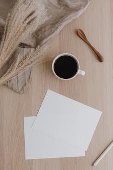 ベージュの木製テーブルに白紙のシート。洗ったリネン毛布、コーヒーカップ、パンパスグラスのアーティストホームオフィスデスクワークスペース