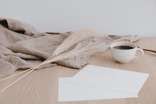 베이지 색 나무 테이블에 빈 종이 시트. 세척 된 린넨 담요, 커피 컵, 팜파스 잔디가있는 아티스트 홈 오피스 데스크 작업 공간