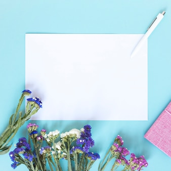 Blank paper sheet; pen and bunch of colorful flowers on blue backdrop