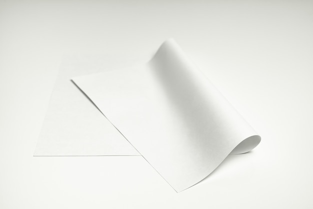 Blank paper sheet on white background. close-up view of bent white paper laying on clean white table top