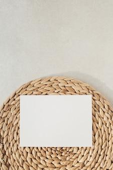 Чистый лист бумаги с копией пространства для макета, соломенная подставка на бетонной поверхности