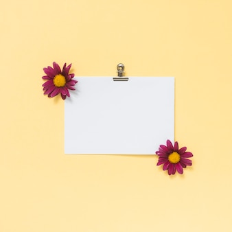 Blank paper sheet with small flowers on table