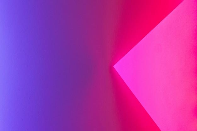 ネオン紫色の照明で巻かれた空白の紙のシートをクローズアップ