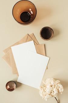 베이지 색 표면에 텍스트, 봉투, 수국 꽃을위한 빈 복사본 공간이있는 빈 종이 시트