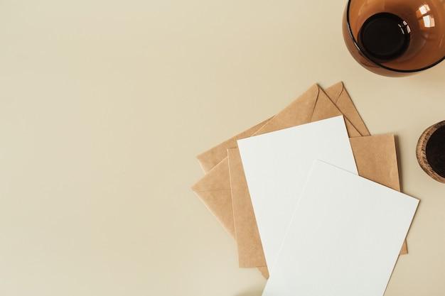 텍스트에 대 한 빈 복사본 공간, 베이지 색 표면에 봉투와 빈 종이 시트