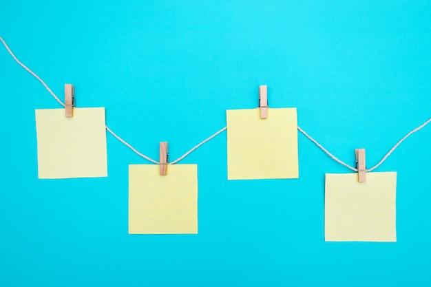 Чистые бумажные наклейки висят на веревке с деревянными прищепками. копировать место для заметок