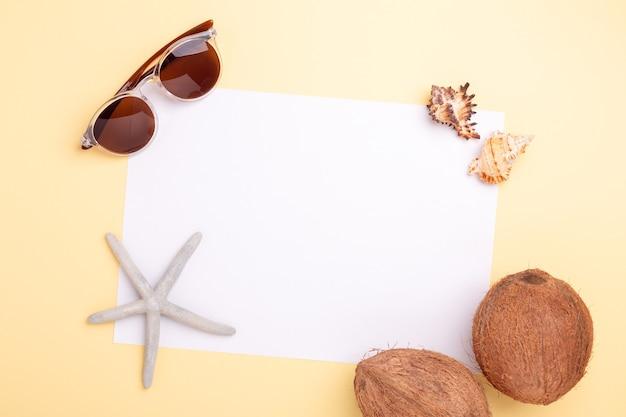 Чистый лист бумаги, солнцезащитные очки, кокосы, ракушки и морские звезды на желтом фоне.