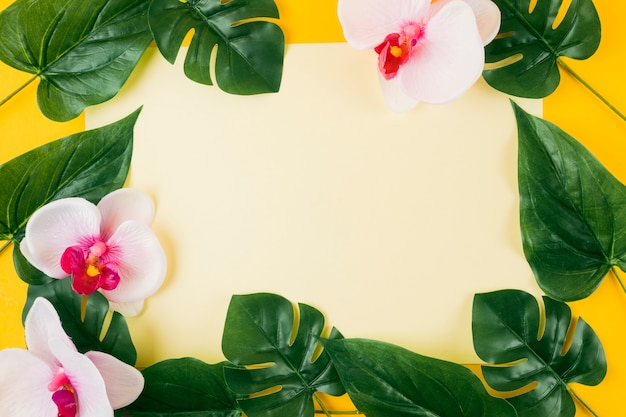 Blank paper surrounded with artificial leaves and orchid flowers on yellow background