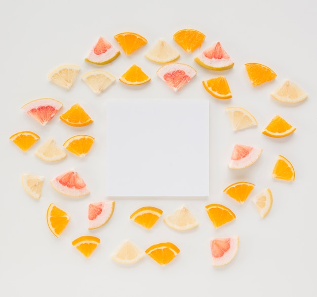 Blank paper surrounded with triangular citrus fruits slices on white backdrop