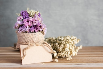Blank paper tag and dry flowers on wooden table