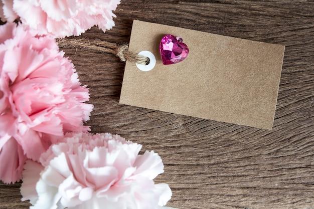 나무 배경에 카네이션 꽃을 가진 빈 종이 태그